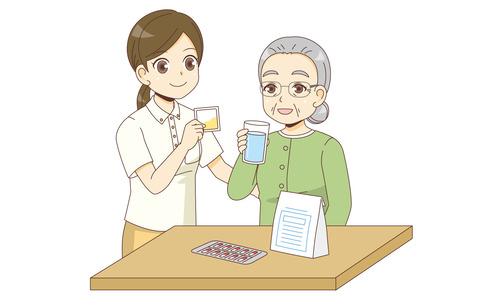 薬を飲む女性高齢者を見守る介護職(薬・服薬/介護・生活)