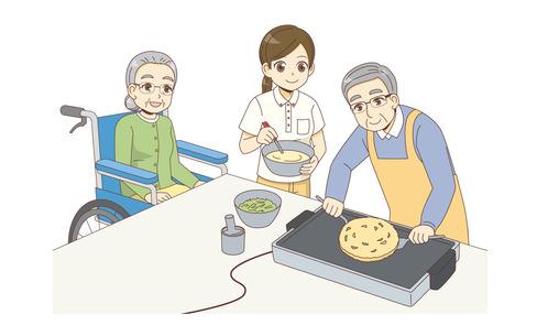 レクリエーションでお好み焼きをつくる男女の高齢者と女性介護職(レクリエーション・イベント/介護・生活)